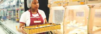 African American woman with tray of bread working at bakery.