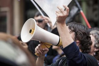Unidentified young demonstrator with megaphone and notebook protesting.