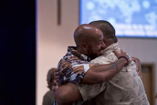 Two African American / Latino men smiling and hugging tightly.