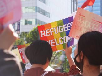 Group of people welcoming LGBT refugees.